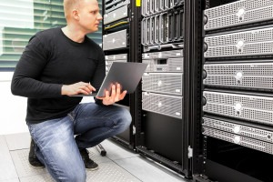 Consultant With Laptop Monitoring Servers In Datacenter
